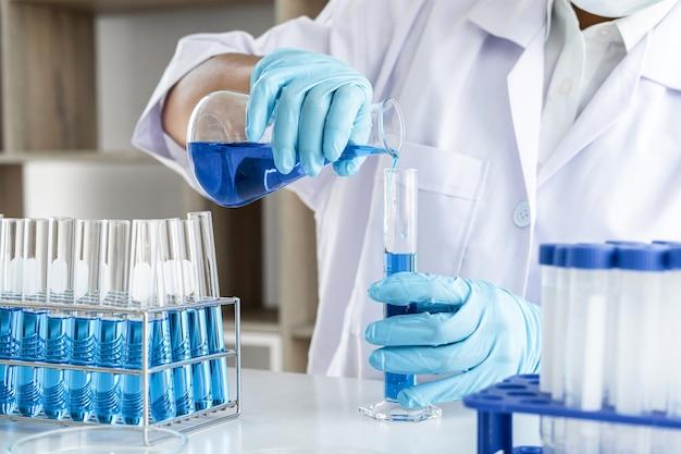 Scientifique en blouse de laboratoire tenant le tube à essai avec à l'aide de réactif avec goutte de liquide de couleur sur l'équipement