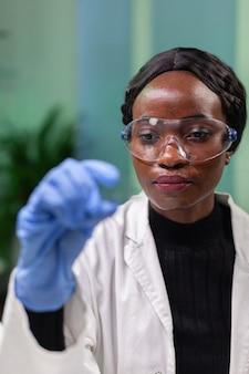 Scientifique de chercheur de botaniste analysant l'échantillon liquide vert sous microscope