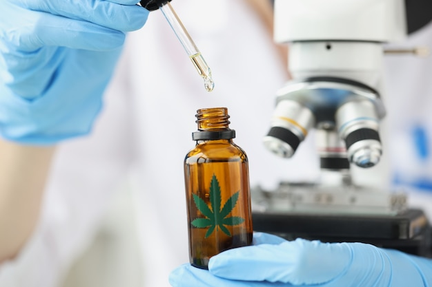Scientifique chimiste examinant l'huile de marijuana au microscope dans la production de gros plan de laboratoire