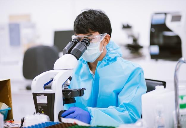 Scientifique en combinaison de protection et masques à l'aide d'un microscope en laboratoire de recherche