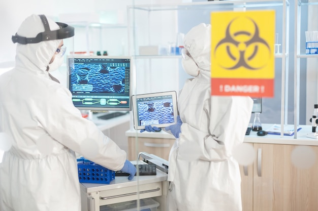 Scientifique dans la zone de danger du laboratoire à l'aide d'un tablet pc vêtu d'un costume ppe. groupe de médecins examinant l'évolution du vaccin à l'aide de la haute technologie pour le diagnostic contre covid19.