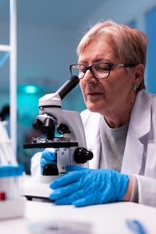Scientifique expérimenté ingénierie échantillon de sang de soins de santé à l'aide d'un microscope