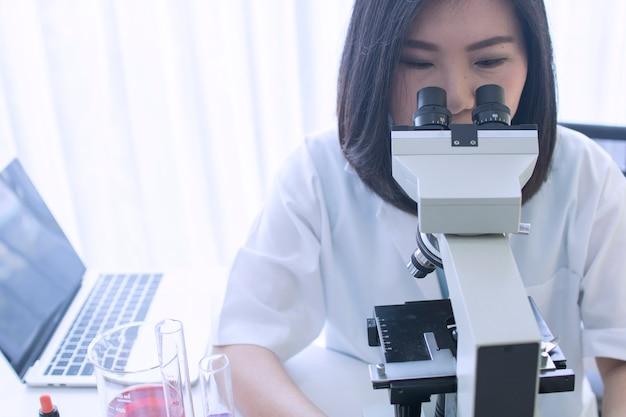 Scientifique expérimenter un liquide chimique en regardant au microscope