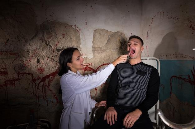Scientifique fou tenant un appareil médical devant un patient dans un cachot avec des murs ensanglantés dans un concept d'horreur d'halloween