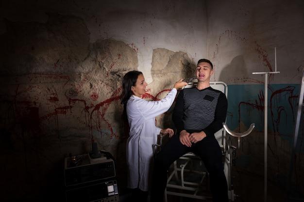 Scientifique fou tenant des pinces médicales devant un patient dans un cachot avec des murs ensanglantés dans un concept d'horreur d'halloween