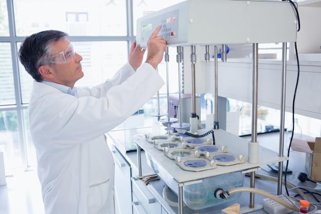 Scientifique avec des lunettes de sécurité en utilisant la machine