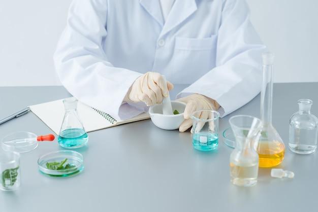 Scientifique ou médecin faisant de la phytothérapie avec des feuilles d'herbes