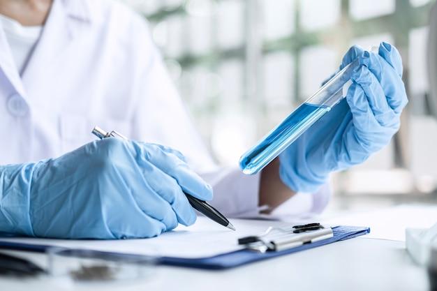 Scientifique ou médical en blouse de laboratoire tenant le tube à essai avec réactif