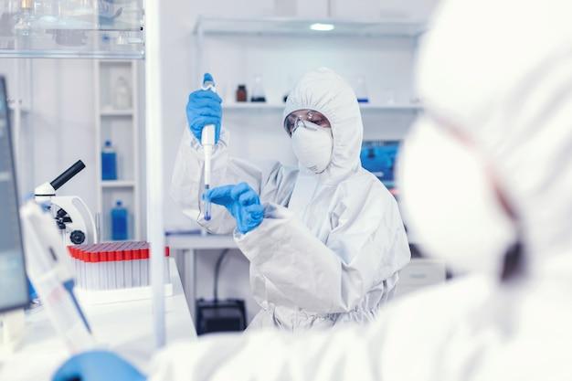 Un scientifique médical développant un vaccin contre le coronavirus dans un laboratoire scientifique tenant une micropipette. équipe de microbiologistes dans un laboratoire de recherche menant une expérience pendant une pandémie mondiale avec covid19.