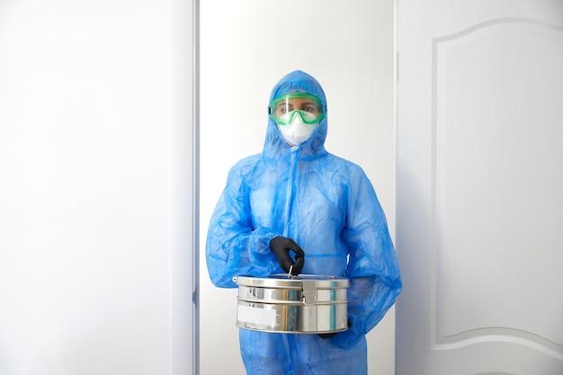 Scientifique médical méconnaissable en uniforme de protection ouvrant les portes et entrant dans la salle de laboratoire tenant un boîtier métallique avec des échantillons.