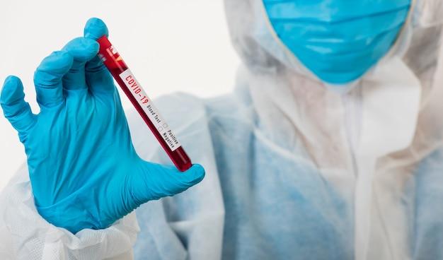 Un scientifique médical en uniforme d'epi porte un masque tenant un échantillon de sang de test de coronavirus d'un tube à essai