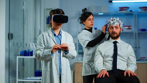 Scientifique neurologique avancé utilisant l'innovation médicale en laboratoire portant des lunettes de réalité virtuelle, gesticulant. équipe de chercheurs travaillant avec le dispositif d'équipement, l'avenir, la médecine, les soins de santé, la vision,