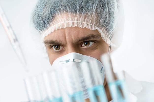 Un scientifique passionné aux yeux bruns dans des vêtements de protection charge des échantillons