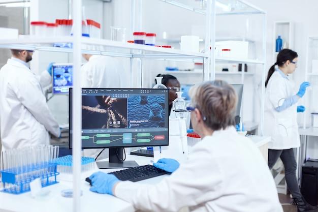 Scientifique principal dans un laboratoire pharmaceutique effectuant des recherches génétiques portant une blouse de laboratoire avec une équipe en arrière-plan. assistant ingénieur africain adn.