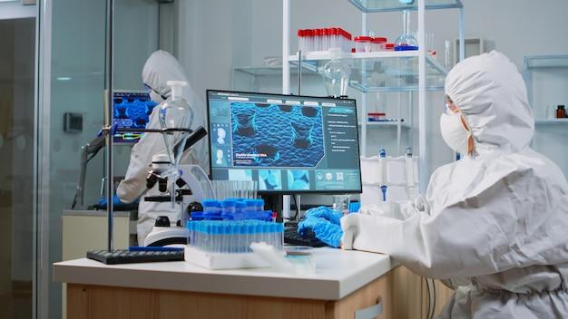 Scientifique de recherche médicale en costume ppe tapant des codes sur pc dans un laboratoire moderne équipé de sciences biologiques appliquées. des ingénieurs de laboratoire mènent une expérience pour le développement d'un vaccin contre le virus covid19