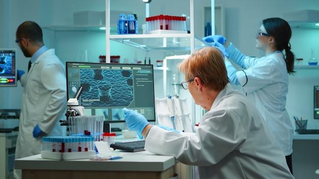 Scientifique de la recherche médicale tapant des codes sur un ordinateur dans le surmenage de laboratoire moderne équipé de sciences appliquées biologiques. des ingénieurs de laboratoire mènent une expérience pour le développement d'un vaccin contre le virus covid19