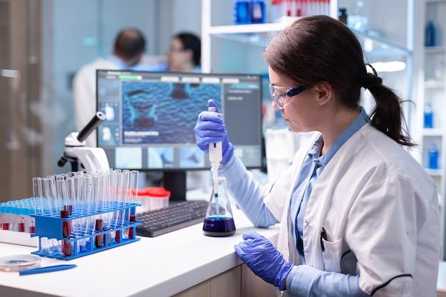 Scientifique regardant l'échantillon dans la micropipette pour le test d'hôpital de biologie