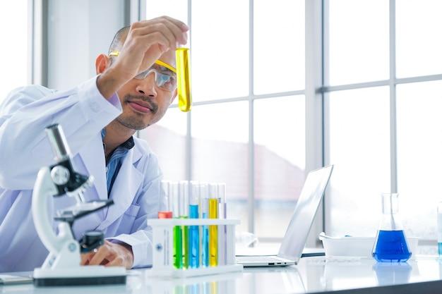 Un scientifique se penche sur l'extraction de l'huile jaune dans un tube à essai
