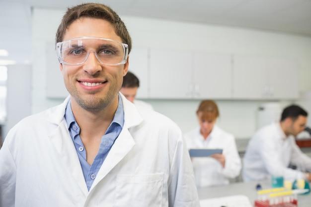 Scientifique souriant avec des collègues au travail dans le laboratoire 2784b70a7753