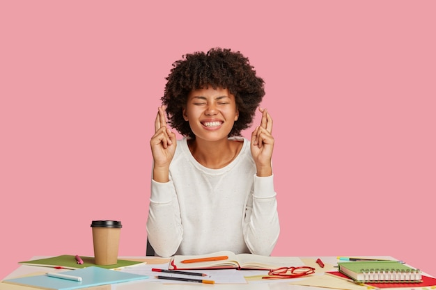 Une scientifique souriante à la peau sombre garde les doigts croisés, pose au bureau, espère une recherche réussie