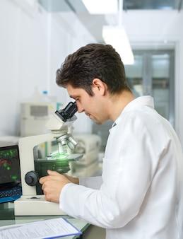 Un scientifique ou un technicien aux cheveux noirs et aux yeux bruns travaille avec des échantillons de microscope