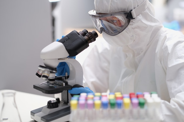 Un scientifique en tenue de protection et masque regarde au microscope. chimiste en salopette travaillant avec divers concept de bactéries