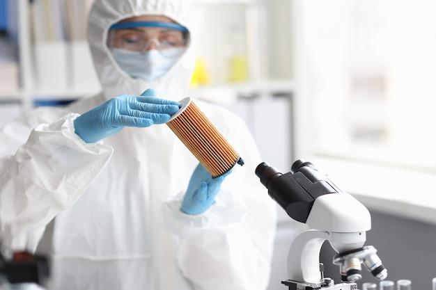 Un scientifique en tenue de protection tient une cartouche filtrante dans un concept de filtre automobile de laboratoire