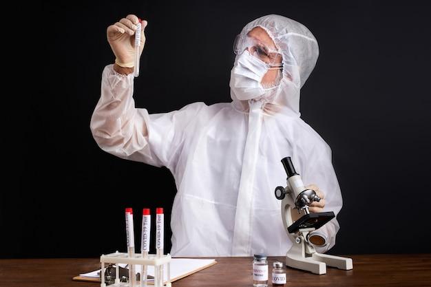 Un scientifique teste un échantillon de tubes biologiques contaminés par le virus corona covid 19, à l'aide d'un microscope