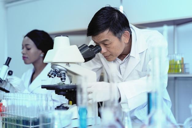 Scientifique utilisant un microscope en laboratoire avec un fond de tube à essai. technologie de santé médicale et concept de recherche et développement pharmaceutique