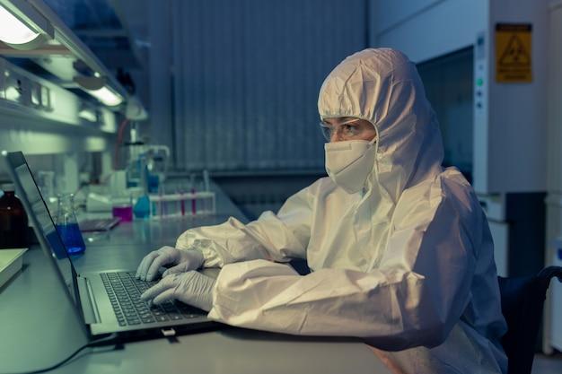Scientifique en vêtements de travail protecteurs et masque tapant sur un ordinateur portable sur son lieu de travail, elle travaille jusque tard dans la nuit dans le laboratoire