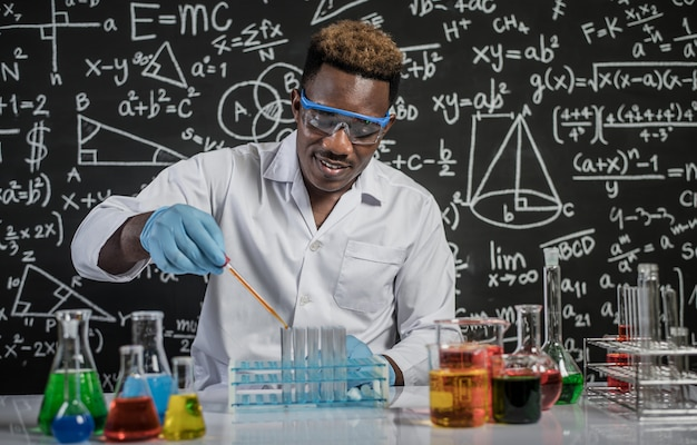 Les scientifiques déposent des produits chimiques orange dans le verre du laboratoire