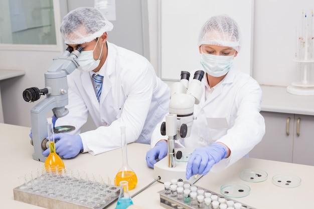 Scientifiques examinant des tubes avec un microscope dans le laboratoire