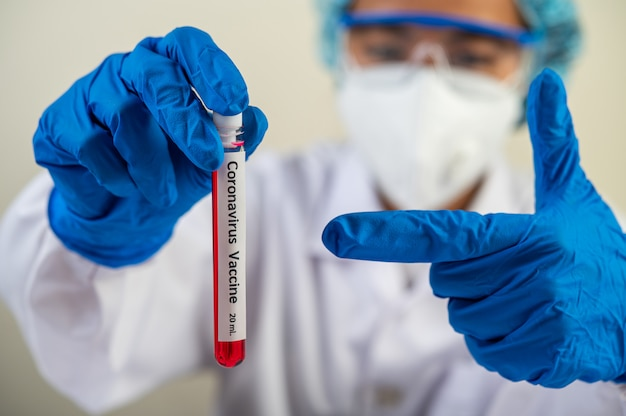 Les scientifiques portent des gants et tiennent des béchers.