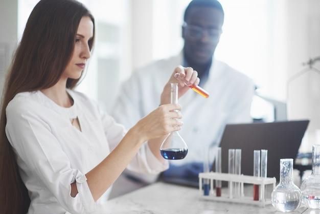 Les scientifiques travaillent en étroite collaboration avec le microscope en laboratoire en menant des expériences et des analyses.