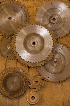 Scies circulaires de différents diamètres suspendus sur une étagère de menuiserie
