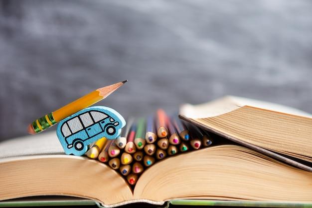 Scolarité. la voiture des enfants monte un livre avec un crayon