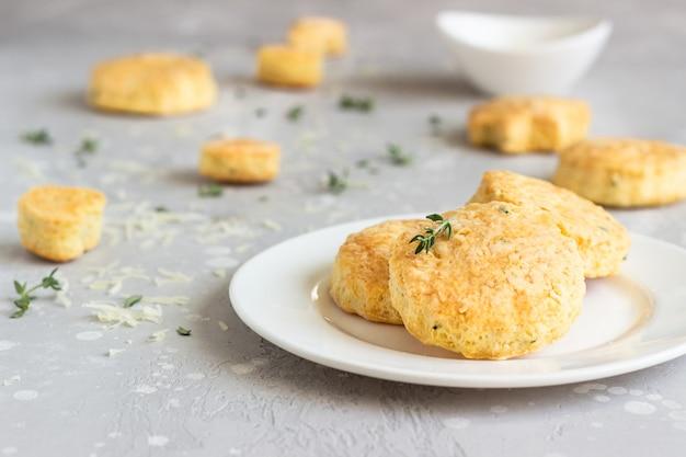Scones ou biscuits salés au fromage et au thym sur une assiette en céramique blanche.