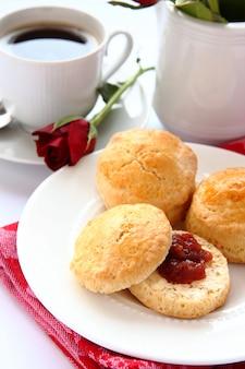 Scones faits maison avec de la confiture de fraises et une tasse de thé