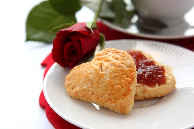 Scones en forme de coeur avec de la confiture de fraises et une tasse de thé