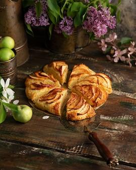 Scones de pomme à la cannelle faits maison avec des fleurs lilas et des branches en fleurs de pomme