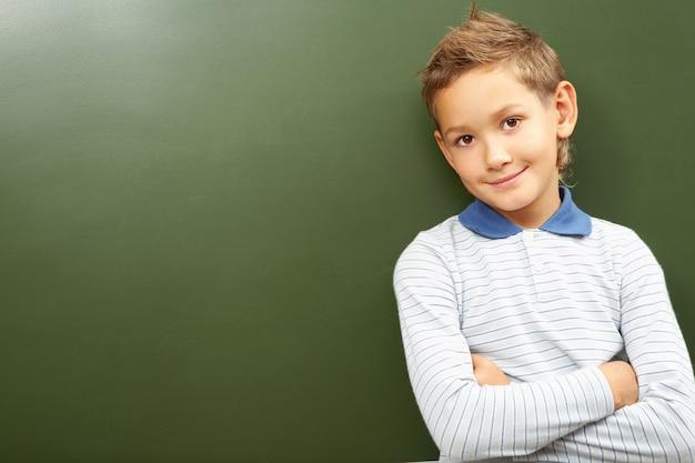 Scoolboy debout en classe près du tableau noir