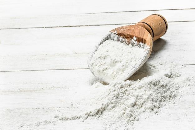 Scoop avec de la farine. sur une table en bois blanche.