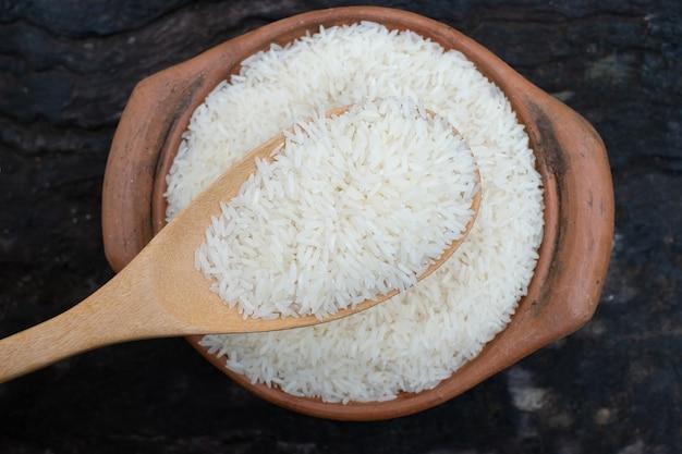 Scoop riz à l'aide d'une louche dans un pot en argile à l'arrière-plan en bois