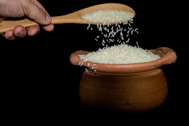 Scoop riz à l'aide d'une louche dans un pot en argile sur fond noir