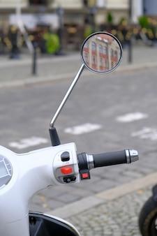 Scooter blanc urbain est garé sur une route pavée dans un centre touristique de la ville