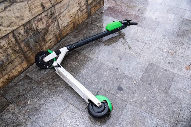 Scooter électrique couché pour le partage sur le sol humide par temps nuageux à bucarest, roumanie