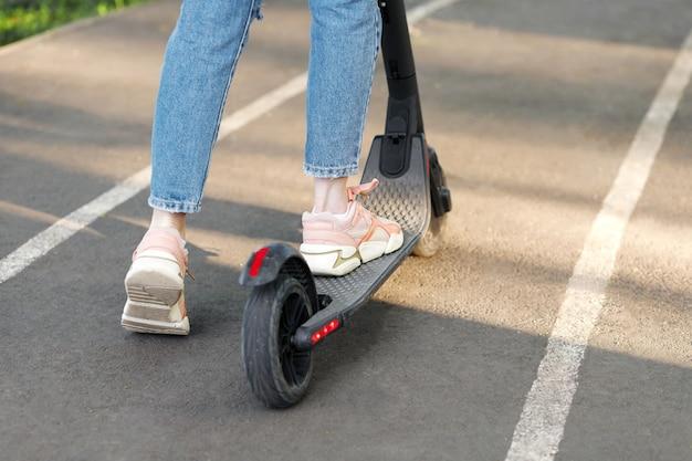 Un scooter électronique et une fille en promenade dans un parc de la ville en été en gros plan