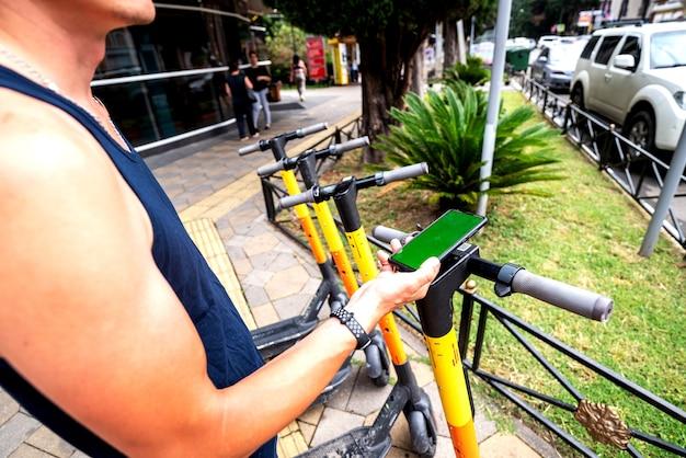 Scooter elero et téléphone portable. homme utilisant le service de location de véhicule e avec smartphone dans la rue et le parc de la ville urbaine. jeune homme loue un transport écologique en été. parking pour scooter électrique.
