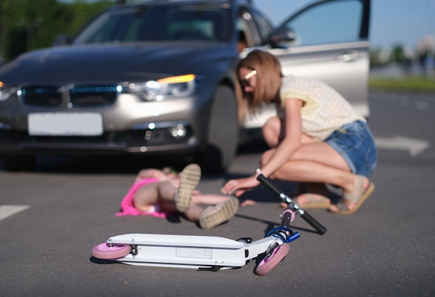 Scooter d'enfants se trouvant sur le fond de la petite fille blessée et de la conductrice de femme de plan rapproché de voiture