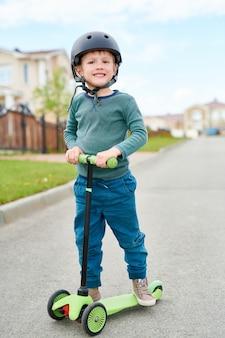Scooter d'équitation de petit garçon souriant